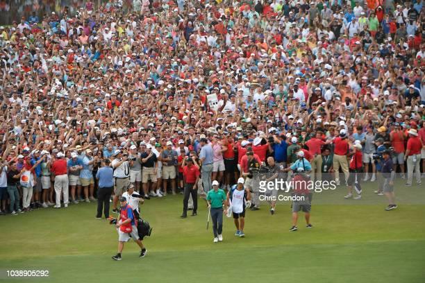 Tiger Woods and Rory McIlroy of Northern Ireland walk to the 18th green during the final round of the TOUR Championship at East Lake Golf Club on...