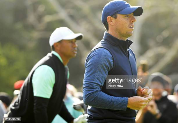 Tiger Woods and Rory McIlroy of Northern Ireland watch a shot on the 2nd hole during the continuation of the first round of the Genesis Open at...