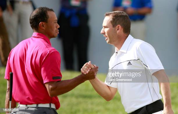 Tiger Woods and Sergio Garcia of Spain shake hands on the 18th green during the Third Round of the BMW Championship at Conway Farms Golf Club on...