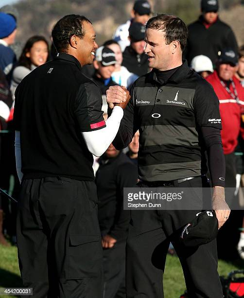 Tiger Woods and Zach Johnson shake hands after finishing their rounds during the third round of the Northwestern Mutual World Challenge at Sherwood...