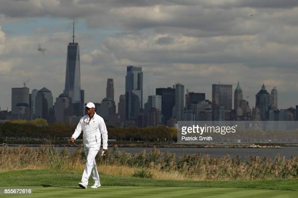 Tiger Woods Captains Assistant of the US Team walks in front the New York City skyline during Friday fourball matches of the Presidents Cup at...