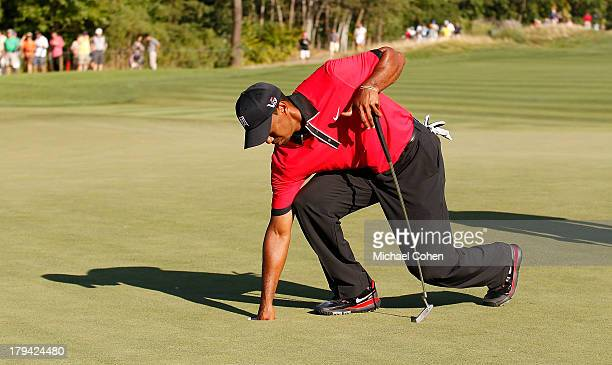 Tiger Woods carefully bends down to remove his ball from the 15th hole after injuring his back during the fourth round of The Barclays held at...
