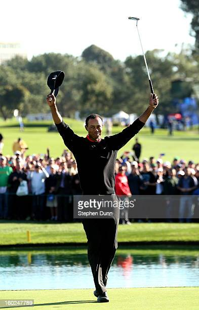 Tiger Woods celebrates after making the final putt for the victory during the final round of the Farmers Insurance Open on the South Course at Torrey...