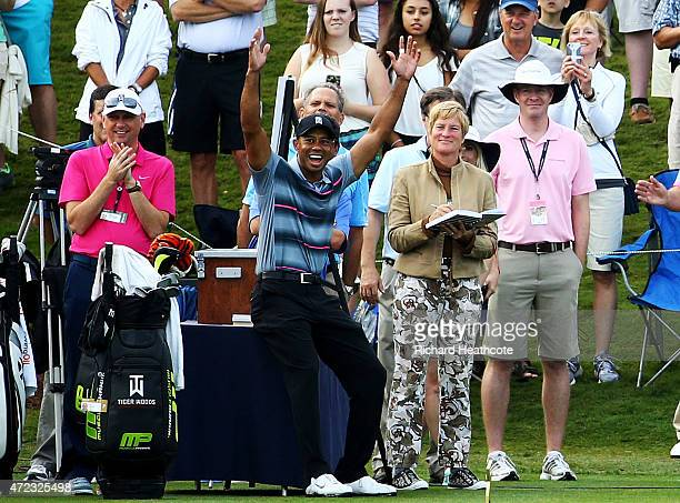 Tiger Woods celebrates as his caddie Joe LaCava plays a shot onto the 17th green during a practice round for THE PLAYERS Championship at the TPC...