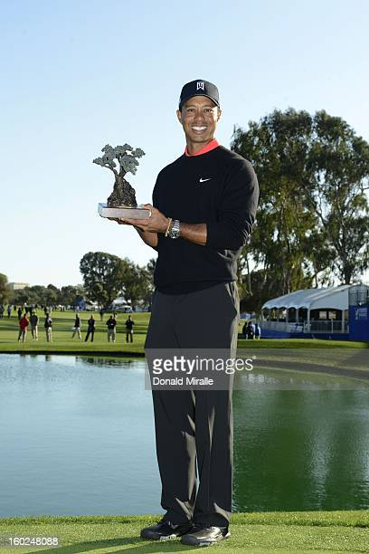 Tiger Woods celebrates his 14 under win with the winner's trophy during the Final Round at the Farmers Insurance Open at Torrey Pines Golf Course on...