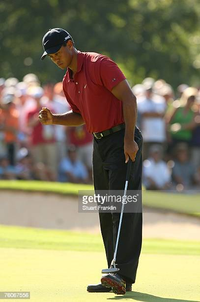 Tiger Woods celebrates his birdie putt on the 15th hole during the final round of the 89th PGA Championship at the Southern Hills Country Club on...