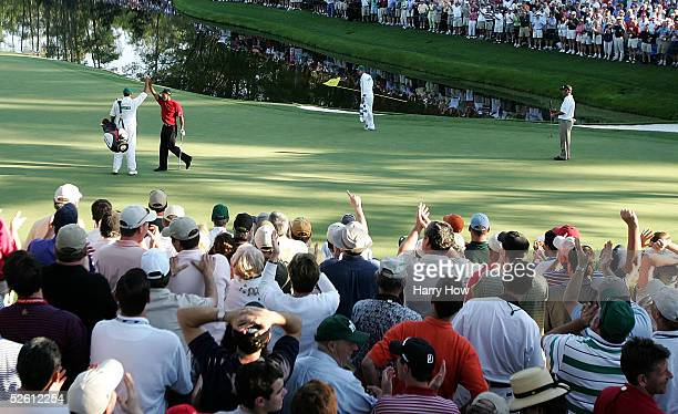 Tiger Woods celebrates with his caddie Steve Williams after chipping in for birdie on the 16th hole during the final round of The Masters at the...