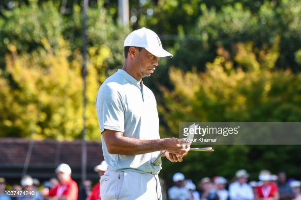 Tiger Woods checks his yardage book before putting for birdie on the 14th hole green during the second round of the TOUR Championship, the final...