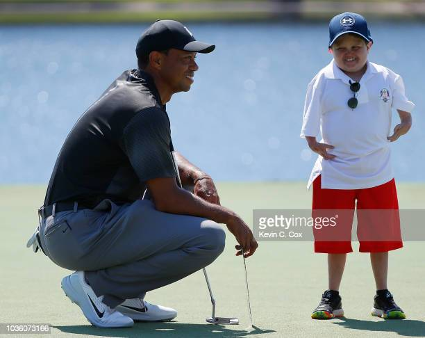 Tiger Woods converses with Asher McGee, a student correspondent from Drew Charter School, while on the putting green during practice for the TOUR...