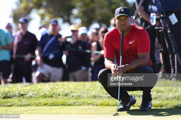 Tiger Woods eyes a putt on the 1st hole on the South Course during the final round of the Farmers Insurance Open golf tournament at Torrey Pines...