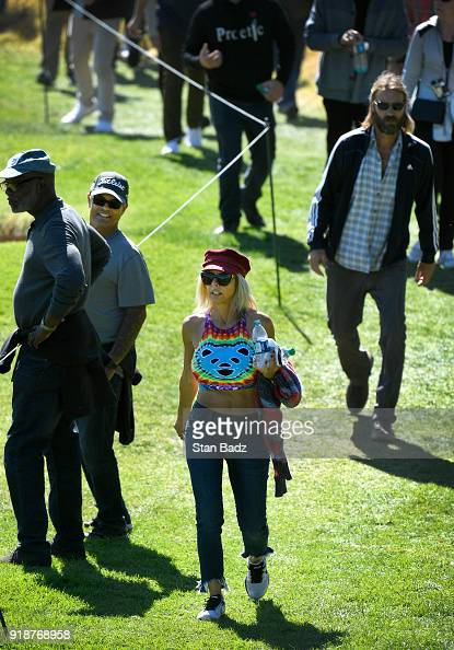 A Tiger Woods fan walks along the ninth hole during the ...