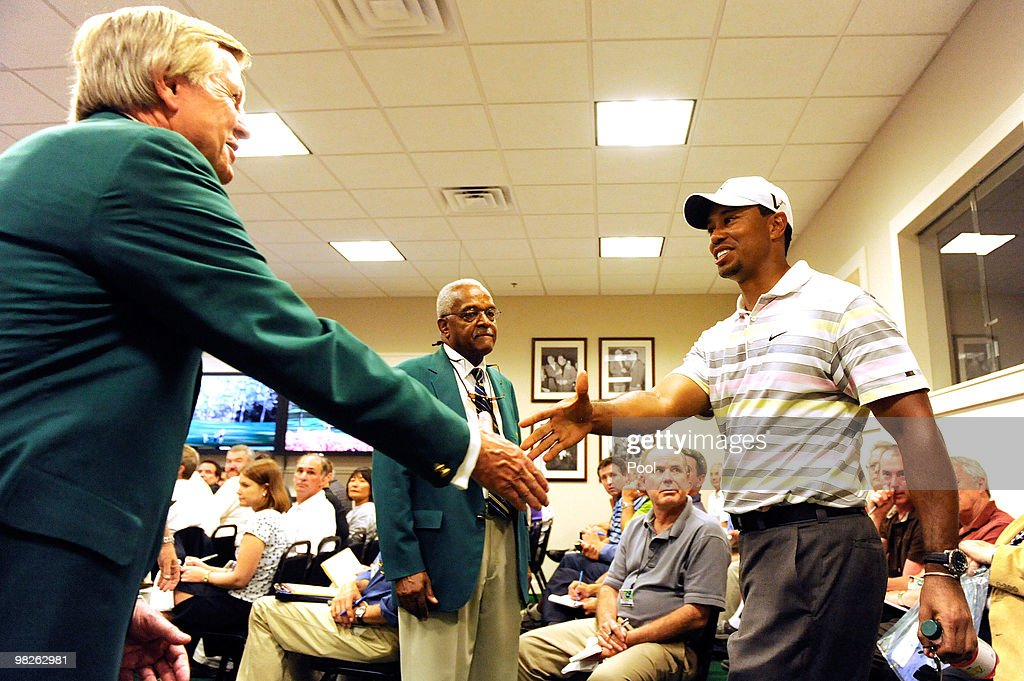 Tiger Woods (R) greets two members of Augusta National Golf Club as he walks into a press conference to address members of the media prior to the 2010 Masters Tournament at Augusta National Golf Club on April 5, 2010 in Augusta, Georgia.
