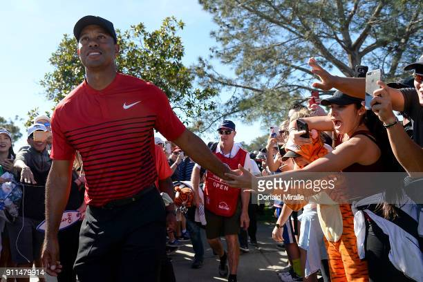 Tiger Woods high fives a fan during the final round of the Farmers Insurance Open at Torrey Pines South on January 28 2018 in San Diego California
