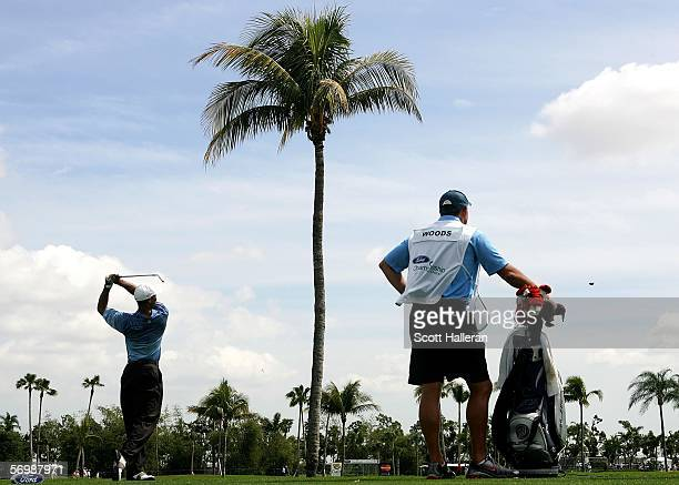 Tiger Woods his a shot to the ninth green as his caddie Steve Williams looks on during the second round of the Ford Championship at the Doral Golf...