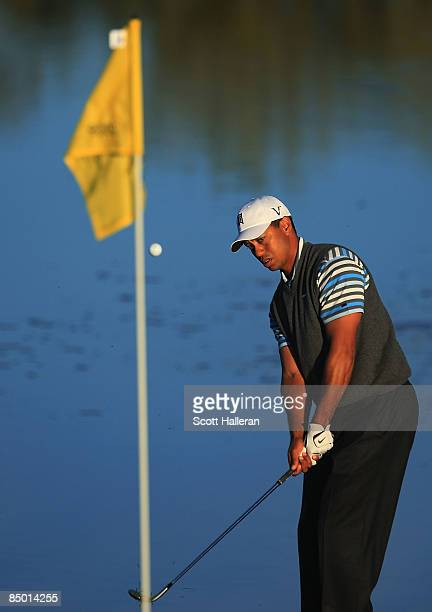 Tiger Woods hits a pitch shot during a practice round prior to the start of the Accenture Match Play Championship at the RitzCarlton Golf Club at...