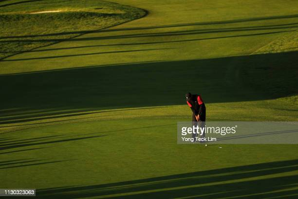 Tiger Woods hits a putt on the 18th hole green during the continuation of the third round of the Genesis Open at Riviera Country Club on February 17,...