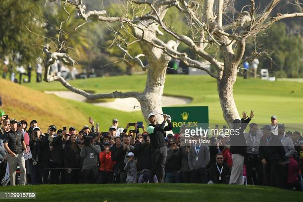 Tiger Woods hits a tee shot on the 4th hole during the continuation of the first round of the Genesis Open at Riviera Country Club on February 15...