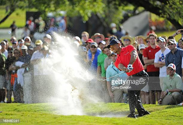 Tiger Woods hits from a bunker on the 12th hole during the final round of the World Golf ChampionshipsCadillac Championship at TPC Blue Monster at...