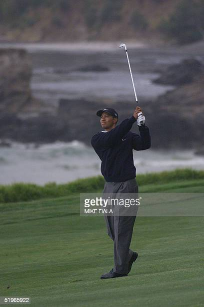 Tiger Woods hits his approach shot on the 10th fairway 16 June 2000 during the second round of the USOpen in Pebble Beach California Woods is the...