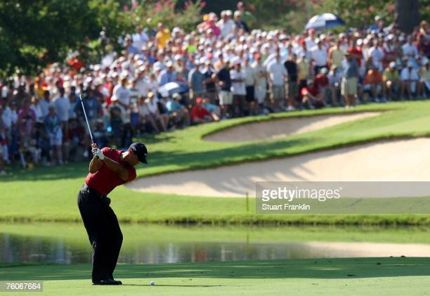 Tiger Woods hits his approach shot on the 13th hole during the final round of the 89th PGA Championship at the Southern Hills Country Club on August...