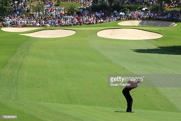 Tiger Woods hits his approach shot on the fourth hole during the final round of the 89th PGA Championship at the Southern Hills Country Club on...