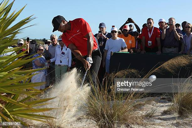 Tiger Woods hits his second shot on the 18th hole from the out-of-bounds waste area as a gallery of fans look on during the final round of the Hero...