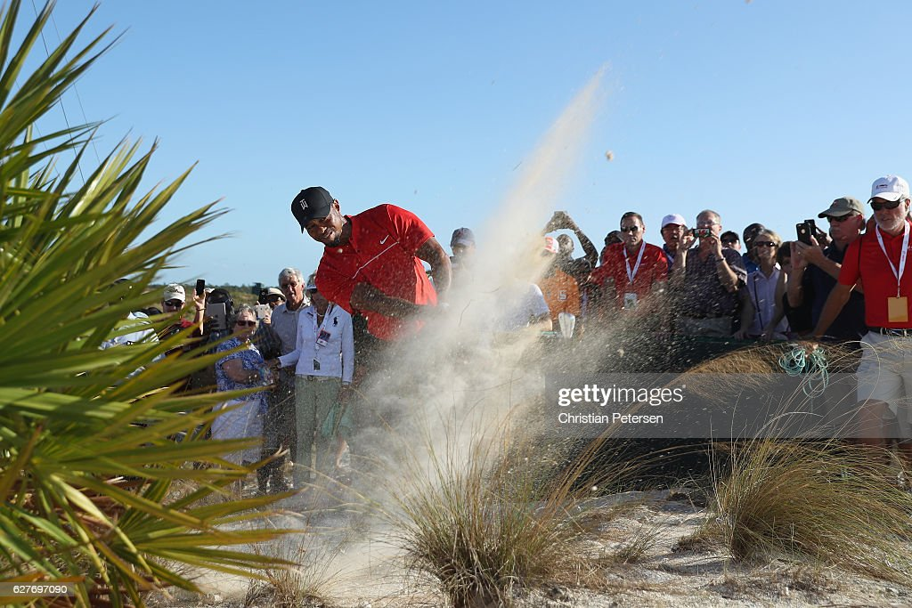 Tiger Woods hits his second shot on the 18th hole from the out-of-bounds waste area as a gallery of fans look on during the final round of the Hero World Challenge at Albany, The Bahamas on December 4, 2016 in Nassau, Bahamas.