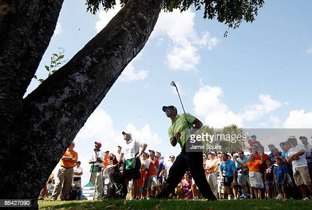 Tiger Woods hits is third shot on the 17th hole from behind a tree during the third round of the World Golf ChampionshipsCA Championship on March 14...