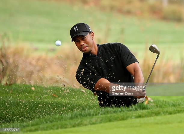 Tiger Woods hits out of a bunker on the fourth hole during the third round of the Tiger Woods World Challenge Presented by Northwestern Mutual at...