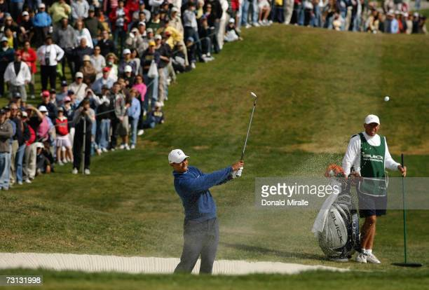 Tiger Woods hits out of the bunker on the 11th hole as caddie Steve Williams watches during the 3rd round of the Buick Invitational on January 27...