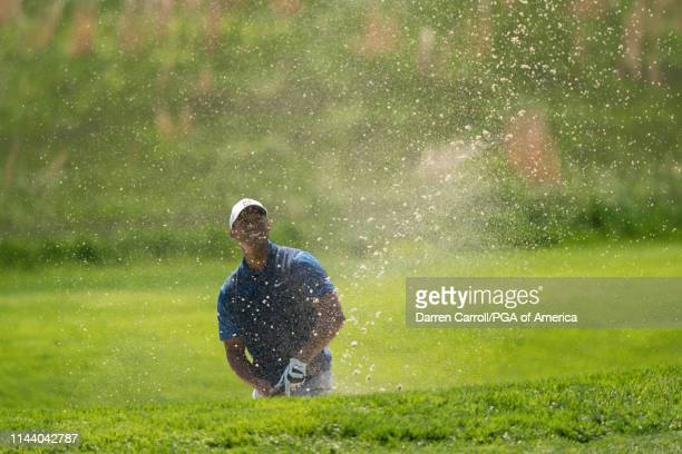 Tiger Woods hits out of the bunker on the 17th hole during the first round of the 101st PGA Championship held at Bethpage Black Golf Course on May...