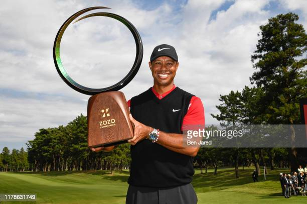 Tiger Woods holds the tournament trophy on the 18th green after the final round of The ZOZO Championship at Accordia Golf Narashino Country Club on...