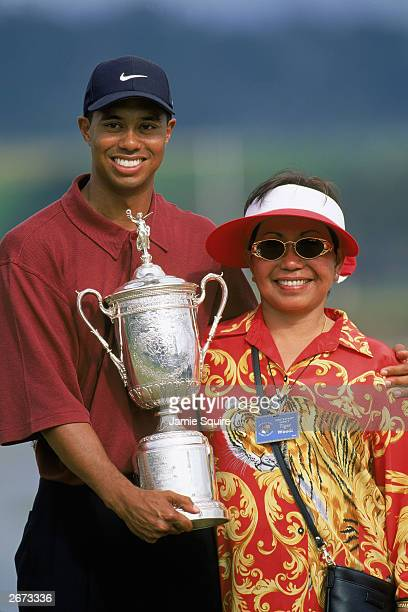 Tiger Woods holds the trophy as he poses with his mother Kultida Woods after winning the 100th US Open at the Pebble Beach Golf Links on June 18,...