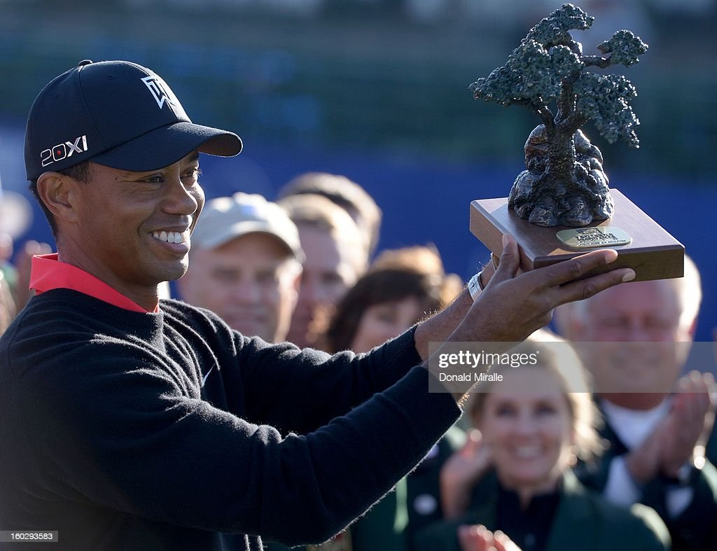 Tiger Woods holds the winner's trophy after his -14 under victory during the Final Round at the Farmers Insurance Open at Torrey Pines Golf Course on January 28, 2013 in La Jolla, California.