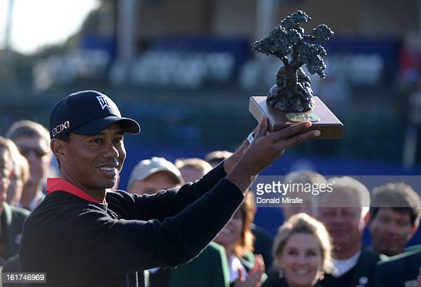 Tiger Woods holds the winner's trophy after his 14 under victory during the Final Round at the Farmers Insurance Open at Torrey Pines Golf Course on...