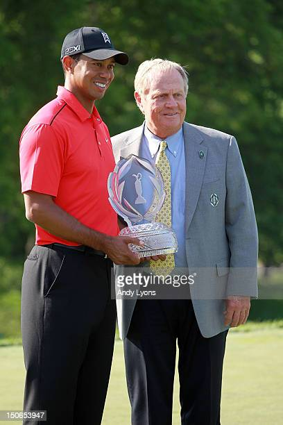 Tiger Woods holds the winner's trophy with Jack Nicklaus following the Memorial Tournament presented by Nationwide Insurance at Muirfield Village...