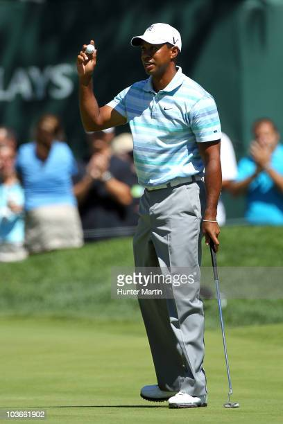 Tiger Woods holds up his ball in reaction to his birdie putt on the 11th green during the second round of The Barclays at the Ridgewood Country Club...
