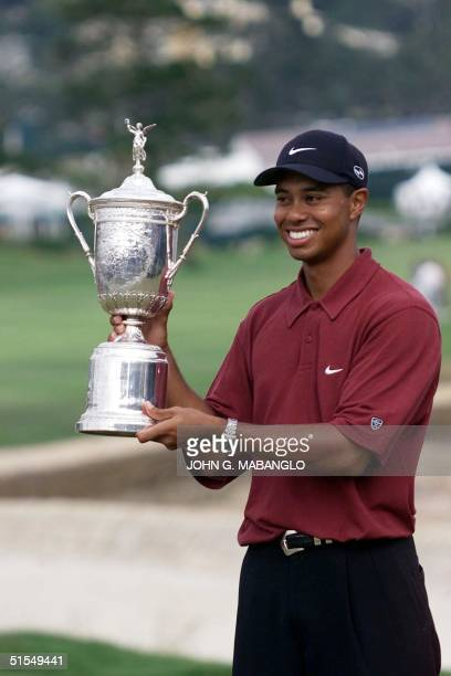 Tiger Woods holds up his US Open Trophy on the 18th Green after winning the tournament at Pebble Beach in California 18 June 2000 Woods won with a...