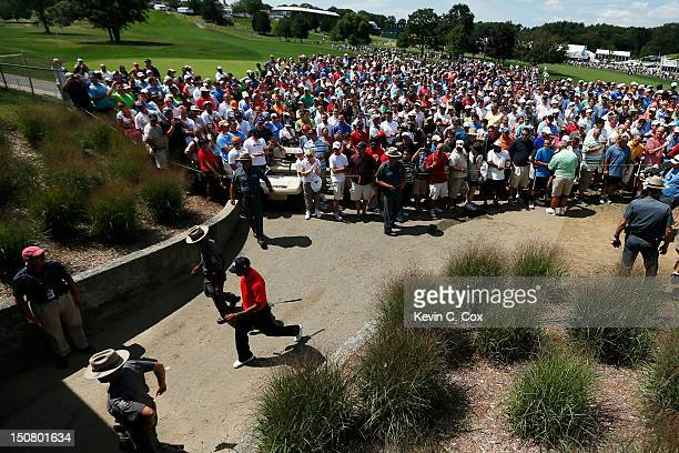 Tiger Woods is accompanied by New York State Police Officers as he walks from the first green to the second tee box during the final round of The...