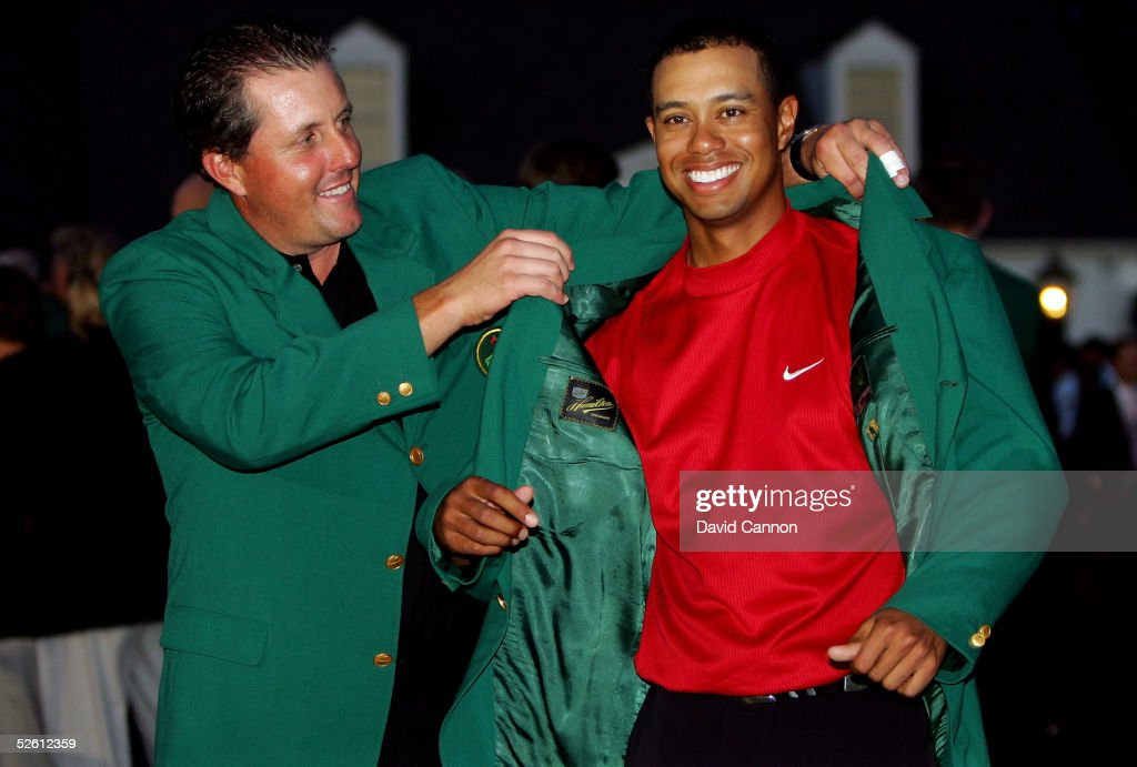 Tiger Woods is presented with the green jacket by Phil Mickelson after Woods won The Masters at the Augusta National Golf Club on April 10, 2005 in Augusta, Georgia.