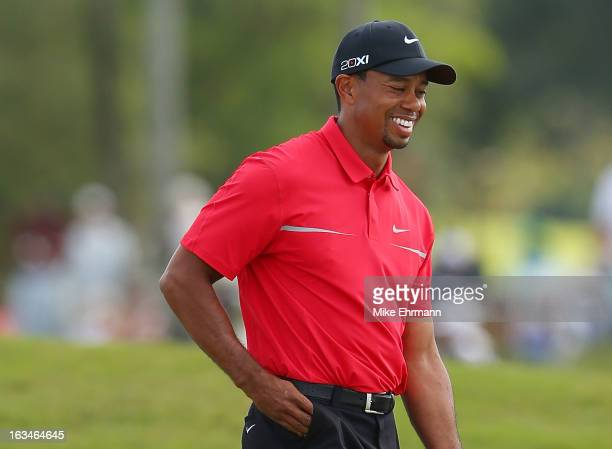 Tiger Woods laughs after a missed putt on the eighth hole during the final round of the World Golf Championships-Cadillac Championship at the Trump...