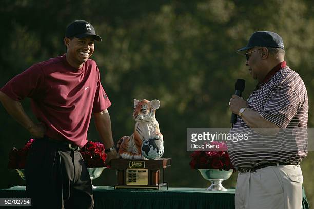 Tiger Woods laughs as his father Earl Woods presents the trophy after the final round of the Target World Challenge at Sherwood Country Club on...