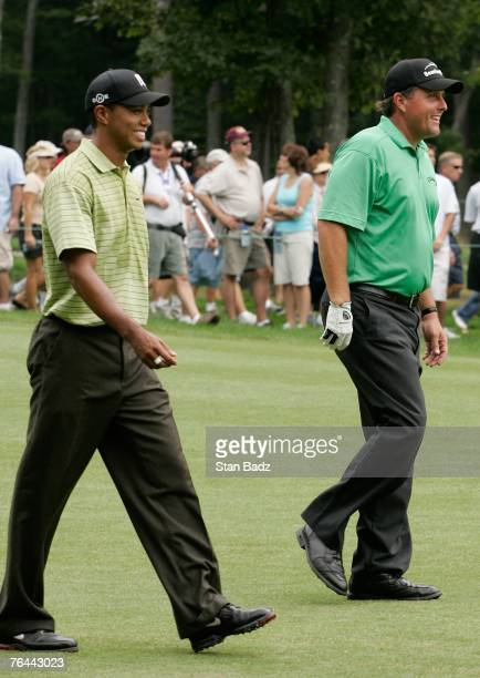 Tiger Woods, left, and Phil Mickelson, right, walk drown the first fairway during the first round of the Deutsche Bank Championship at TPC Boston on...