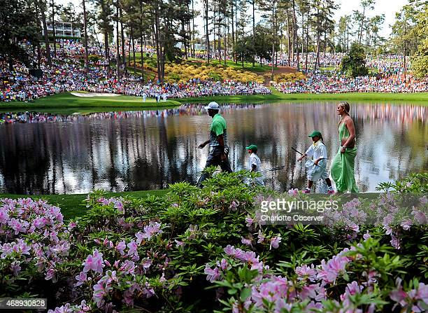 Tiger Woods left leads his son Charlie daughter Sam and partner Lindsey Vonn past the azaleas toward the ninth green during the Par 3 contest on...
