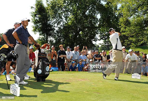 Tiger Woods, left, watches his playing partner Dallas Cowboys Q.B. Tony Romo hit from the seventh tee box during the Pro-Am round for the AT&T...