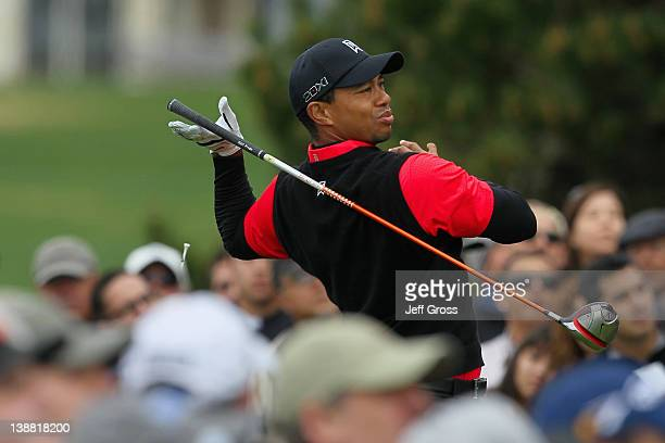 Tiger Woods lets go of his club as he hits his tee shot on the tenth hole as a gallery of fans look on during the final round of the ATT Pebble Beach...