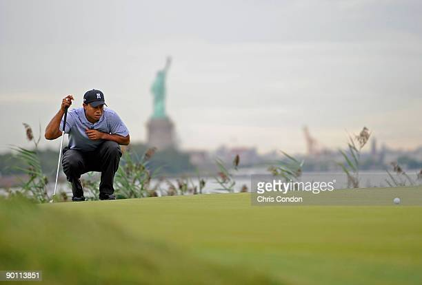 Tiger Woods lines up a par putt on the 14th green during the first round of The Barclays at Liberty National Golf Club on August 27, 2009 in Jersey...