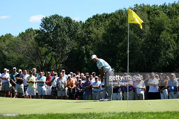 Tiger Woods lines up a putt attempt on the tenth green as fans keep a close watch during the second round of The Barclays at the Ridgewood Country...