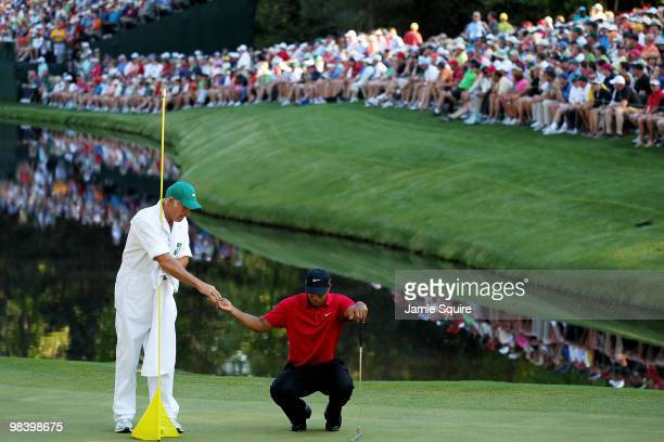 Tiger Woods lines up a putt with the help of caddie Steve Williams in front of a gallery of fans on the 16th green during the final round of the 2010...