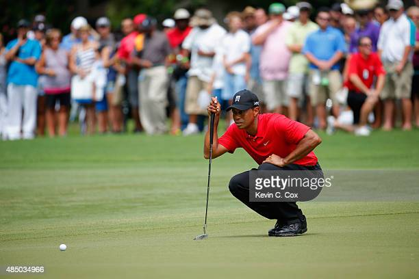 Tiger Woods lines up his birdie putt on the fourth green during the final round of the Wyndham Championship at Sedgefield Country Club on August 23...